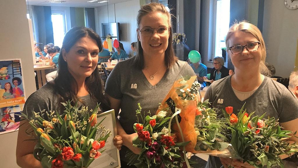 Tre sjukgymnaster håller i blombuketter.