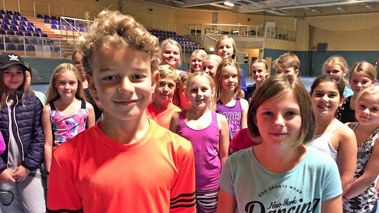 Eleverna Oskar Eklund och Stina Wagander står framför sina klasskamrater i en idrottssal.