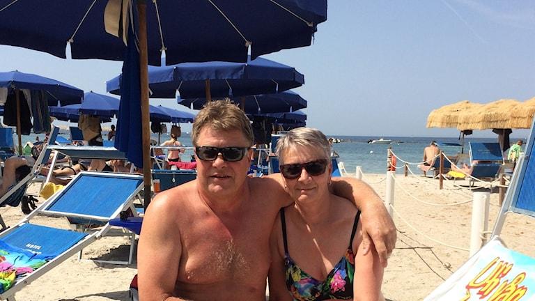 En man och en kvinna sitter i badkläder under ett parasoll på en strand. I bakgrunden fler parasoll och havet.