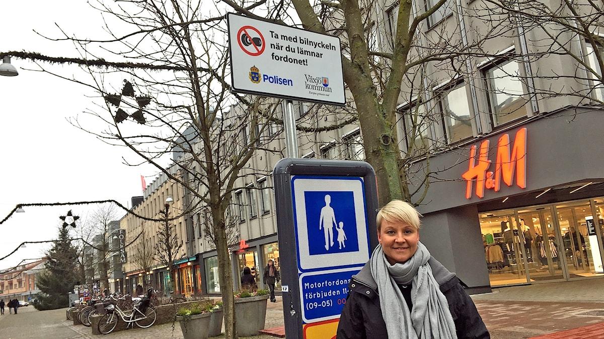 Anna Tenje står på Storgatan i Växjö framför en skylt med texten: Ta med bilnyckeln när du lämnar fordonet