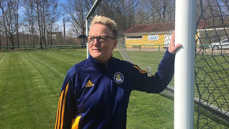 Katarina Palm ordförande i Lessebo GoIF står och håller i ett av de stora målen på fotbollsplanen. I bakgrunden finns den gula klubbstugan. Hon har en mörkblå jacka det står Lessebo GoIF.