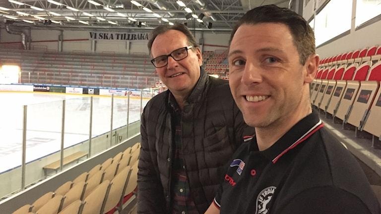 Pelle Wass, ordförande och Daniel Håkansson, klubbchef och assisterande tränare sitter på läktaren i ishallen. Till vänster syns isen.