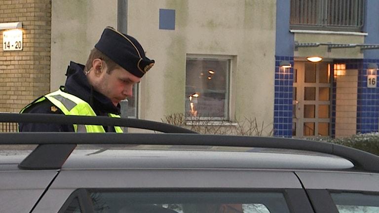 En polis tittar in i en personbil