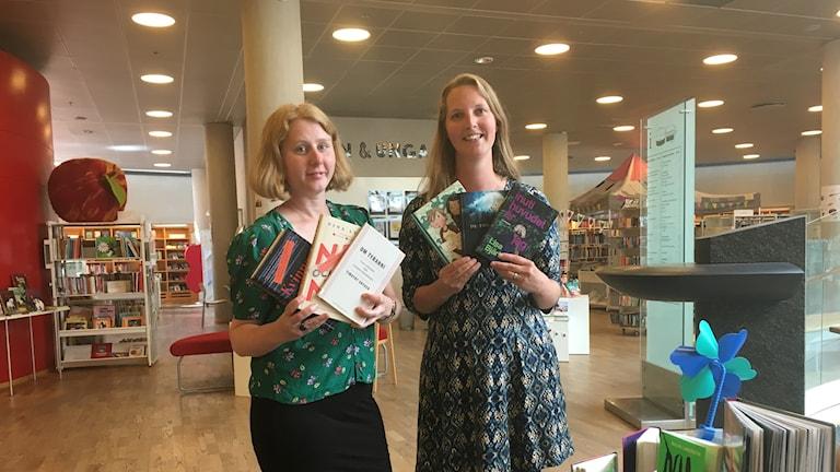 Sofie Petersson och Alexandra Karlsson står och visar sina boktips på biblioteket i Växjö.