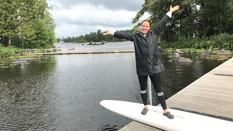 Nathalie Widnemark är fritidsledare vid holmarna står på en surfbräda med händerna utsträckta vid vattnet.