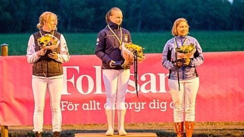 Tre tjejer med ridkläder står på prispallen