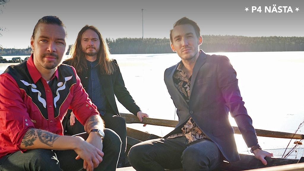 Tre män på en bygga vid en sjö
