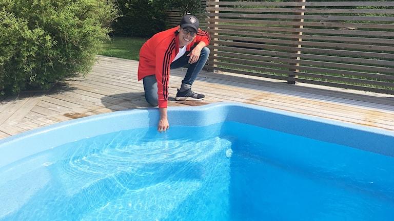 En man sitter vid en poolkant och doppar handen i vattnet.