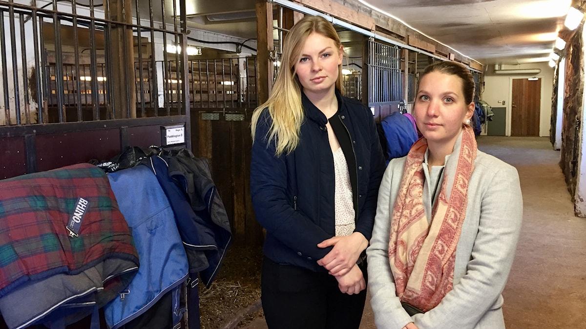 Ryttarna Linn Bengtsson och Lina Ekenberg inne i stallet.