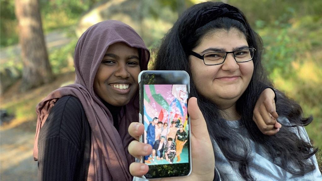 Två tonårstjejer som håller fram en mobiltelefon med bild på en sydkoreansk popgrupp.