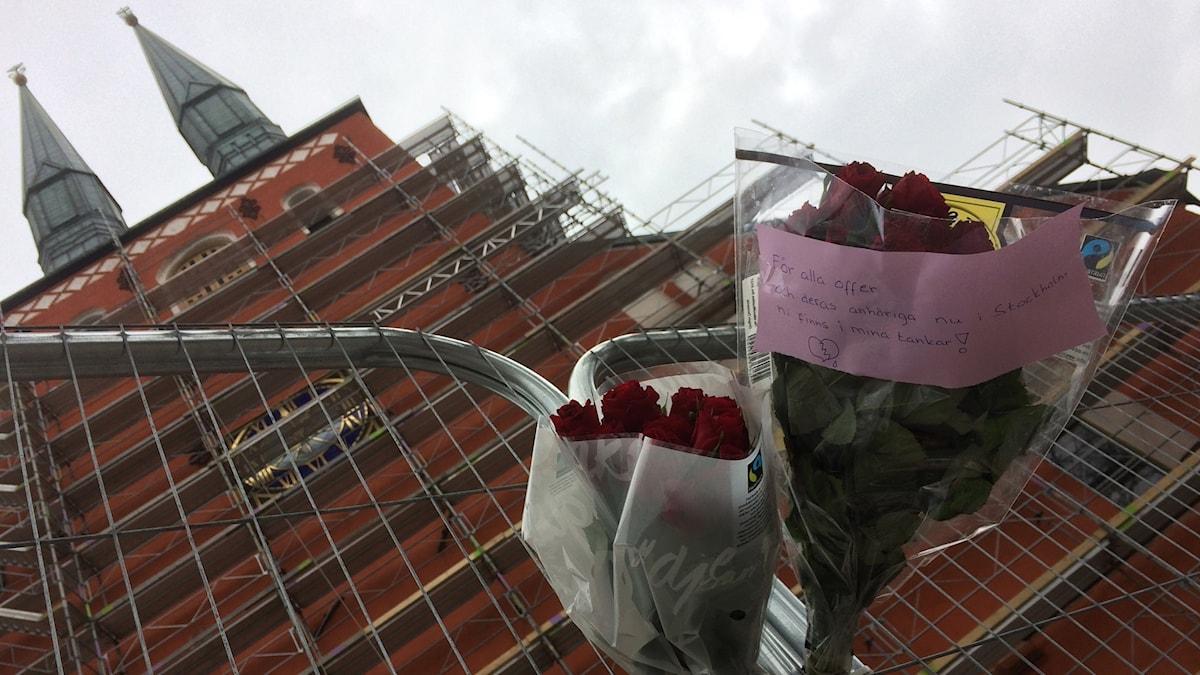 """Blommor utanför Växjö domkyrka där det står """"För alla offer och deras anhöriga nu i Stockholm. Ni finns i mina tankar!"""""""
