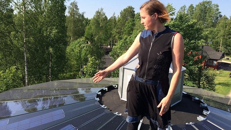 Simone står på sitt tak och pekar på solcellerna