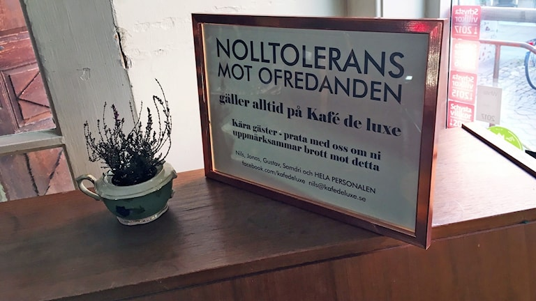 """En skylt med texten """"Nolltolerans mot ofredanden gäller alltid på Kafé Deluxe"""""""