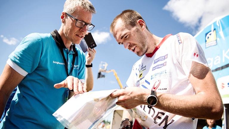 En orienterare och en arrangör tittar ner på en karta.