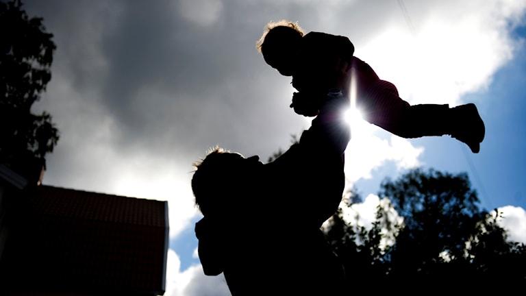 En pappa lyfter ett barn i luften.