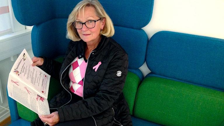 Carina Olsson, ordförande i Bröstcancerföreningen Viktoria sitter och bläddrar i en broschyr.