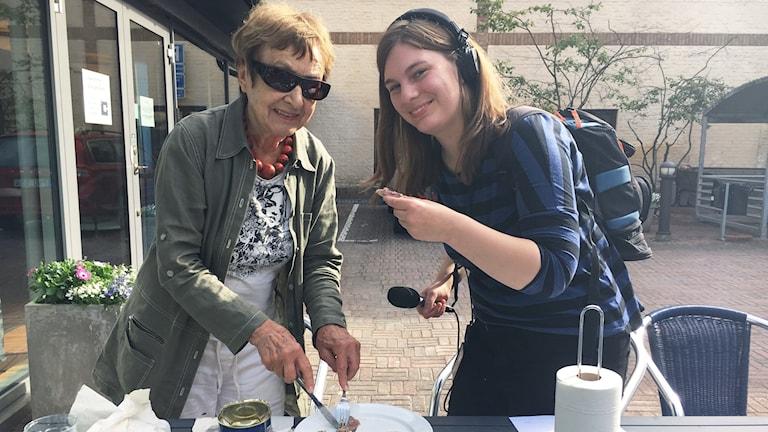 Till vänster äldre kvinna som står och skär i en surströmming med kniv och gaffel. Till höger kvinna med hörlurar och mikrofon som håller i ett knäckebröd med surströmming.