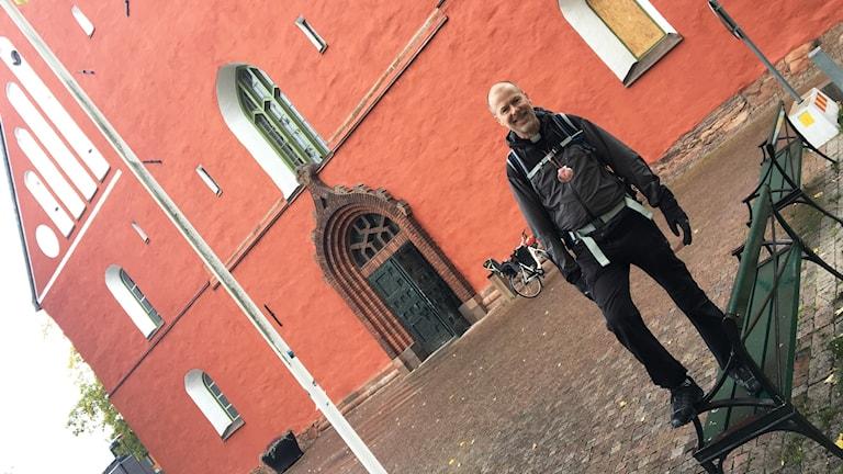 En präst står på en bänk framför Växjö domkyrka. Bilden lutar så det ser ut som att kyrkan ska tippa till vänster.