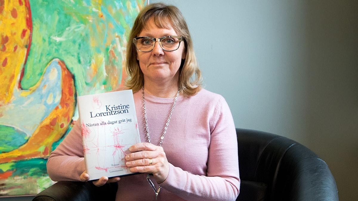 "Kristine Lorentzson håller upp sin bok ""Nästan alla dagar grät jag""."