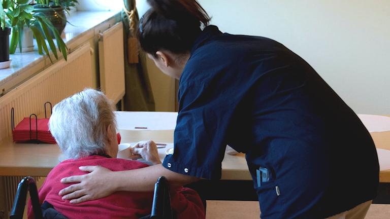 Kvinna i rullstol blir klappad på axeln av vårdperson.