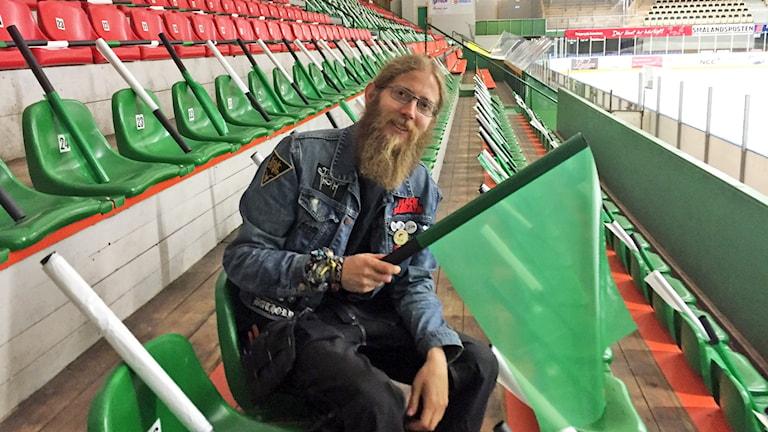 Erik Jacobsson sitter på läktaren och viftar med en grön flagga.