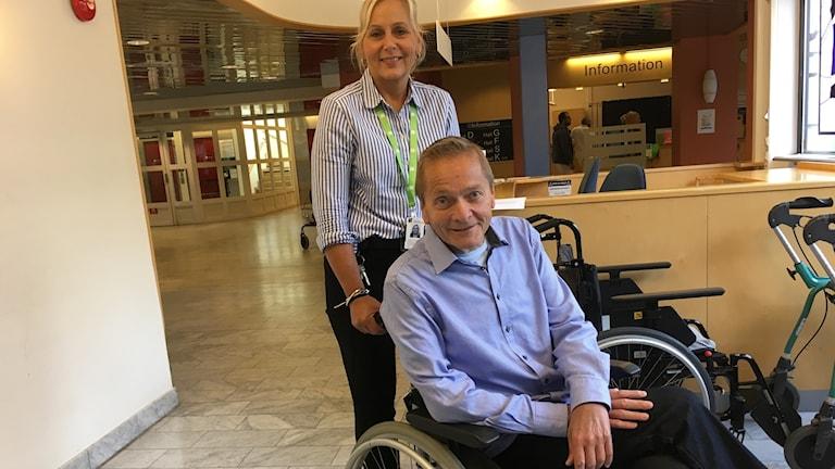 Göran Palmquist sitter i en rullstol och Anniak Elmgren står bakom rullstolen i entréhallen på lasarettet i Växjö