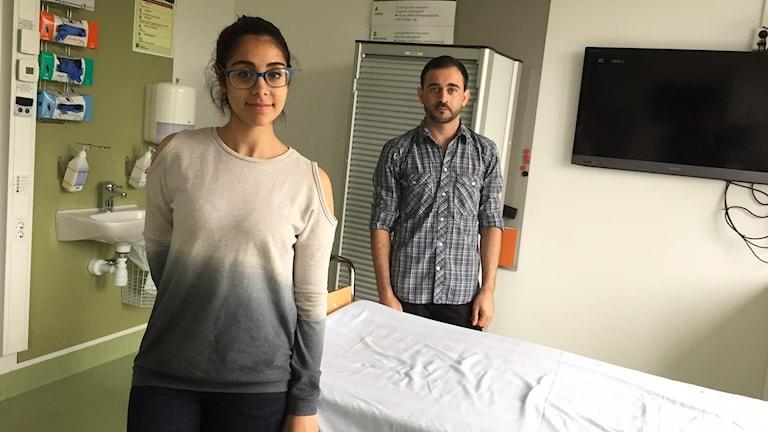 Hanin och Ali står vid en säng i ett vårdrum på lasarettet i Växjö.