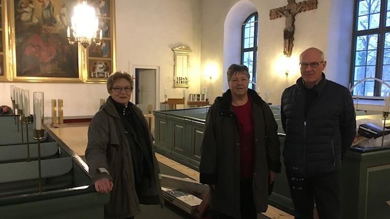 Två kvinnor och en man står mellan bänkraderna inne i en kyrka.