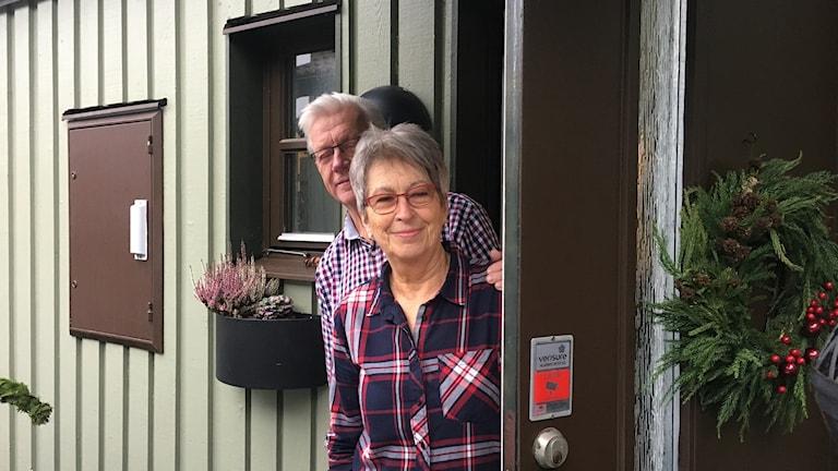 Åke och Liljan tittar ute genom sin ytterdörr som är brun. Den skulle de vilja ha vit istället.