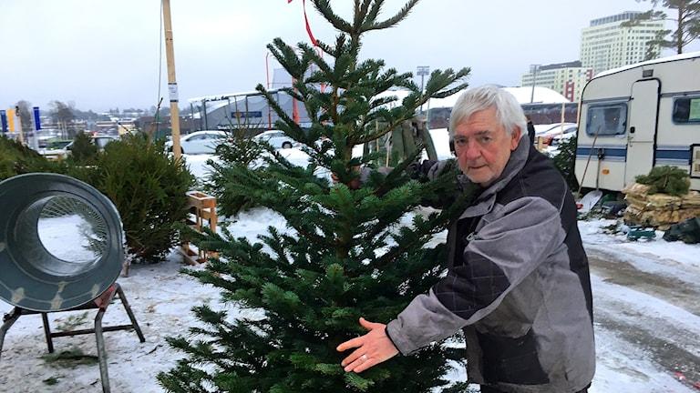 Ulf Bark står ute på en parkering och håller uppen julgran