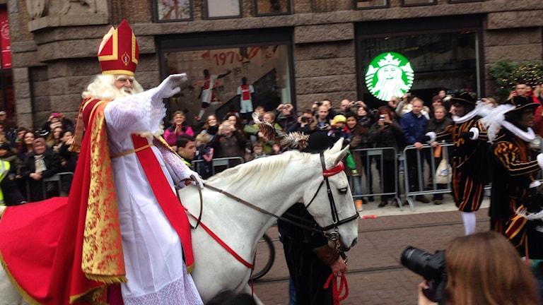 Sinterklaas rider på en häst i en folksamling.