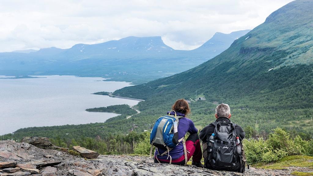 Två personer sitter på en klippa vid en vandringsled och tittar på utsikten.