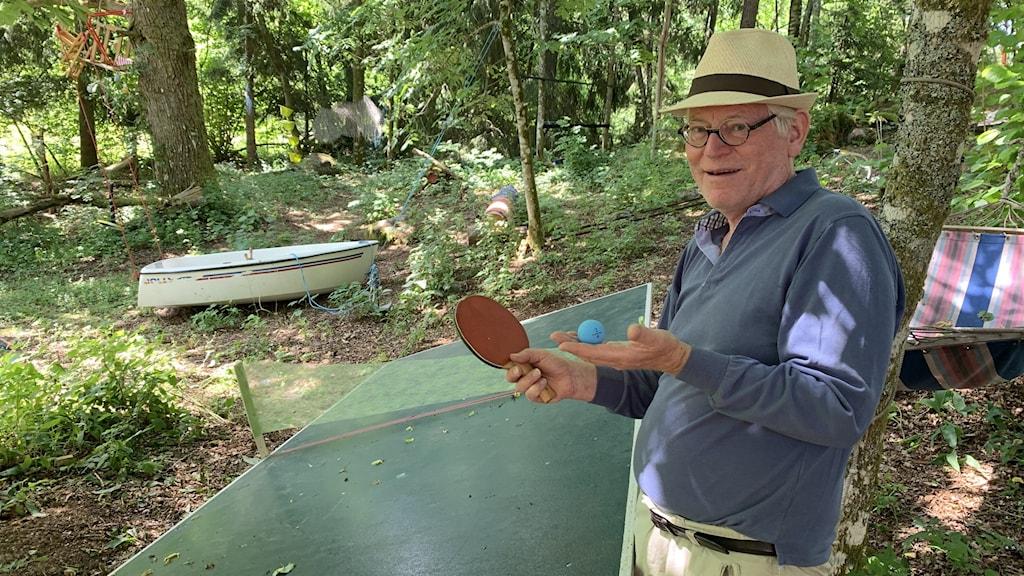 En glad man med pingisracket i högsta hugg framför ett snedvridet pingisbord.