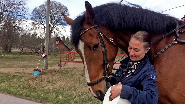 En kvinna håller om en häst med en toarulle i handen.