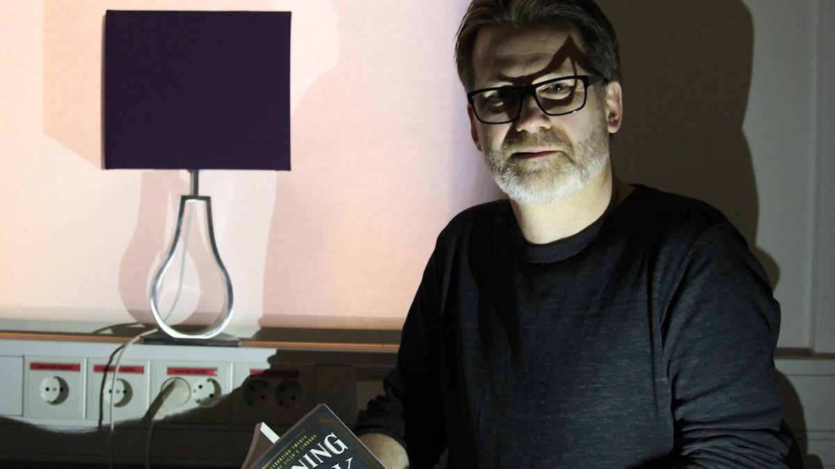 Hans-Åke Lilja sitter i ett dunkelt rum och läser ur sin bok.
