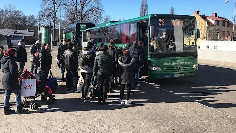 Personer ska gå på en buss.