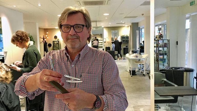 Magnus Lindén håller upp sina verktyg