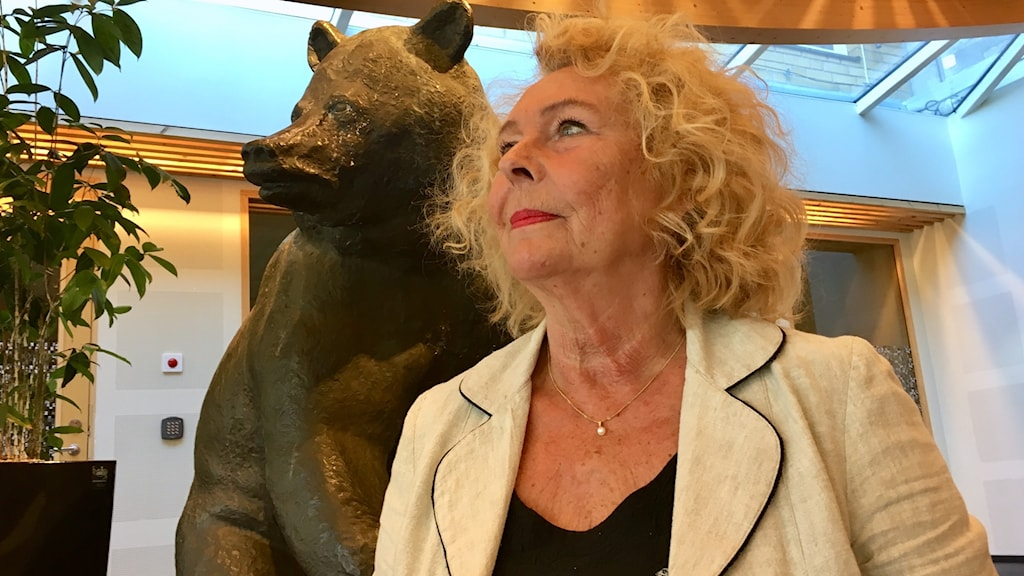 Eva Johansson står vid en staty av en björn.