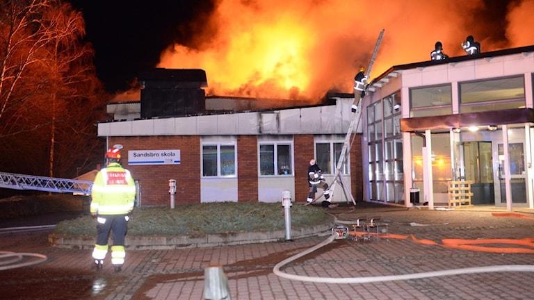 Brand i Sandsbro skola. Flammor upp från taket, brandmän uppe på taket innan byggnaden är övertänd.