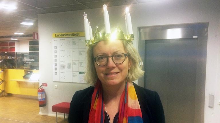Ingrid Persson, kommunikationschef på Linnéuniversitetet står med en luciakrona på huvudet.