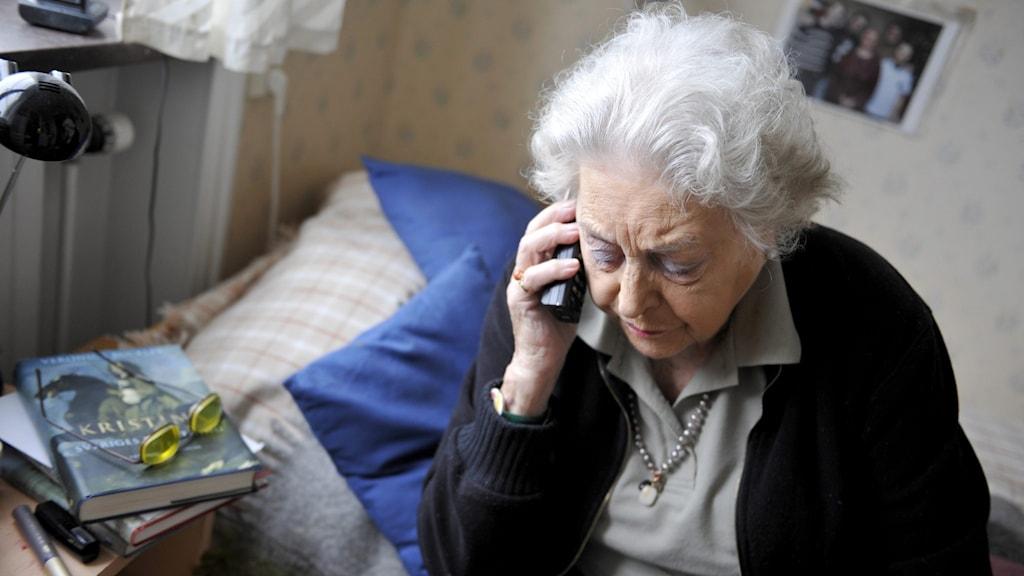En äldre kvinna sitter på sin säng.