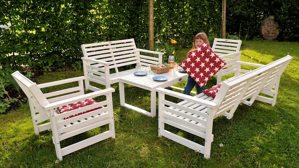 Dukat för fest ute i en trädgård. En flicka springer bland möblerna.