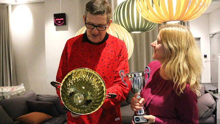 Staffan Kulneff och Kristin Holmberg håller i årets prispokaler och funderar på vems hylla de kommer hamna på?