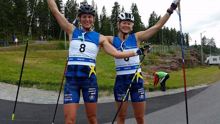 Två glada tjejer i blåvita kläder och med hjälm på huvudena och stavar i händerna.