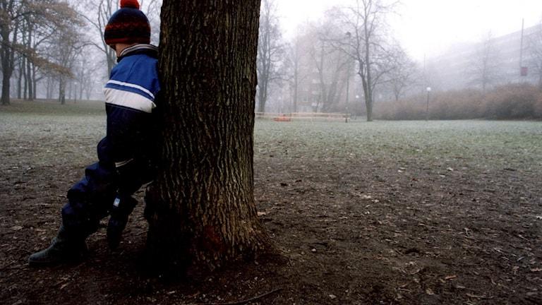 Ett barn som lutar sig mot ett träd