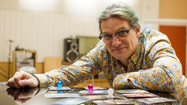 Spelrecensenten Jonas Danielsson framför figurer från ett brädspel