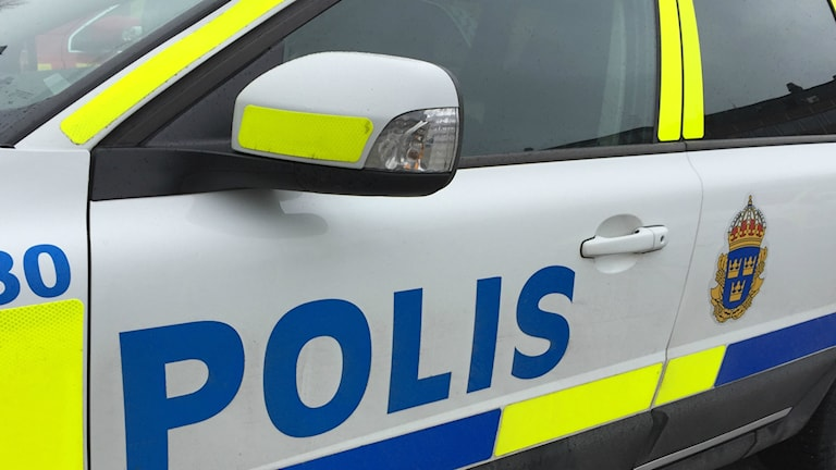 Förardörr och backspegel på polisbil med polisens emblem
