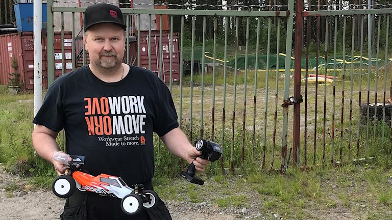 Roger Nordin står utanför RC-banan i Flurkmark och håller i en radiostyrd bil samt tillhörande kontroll.