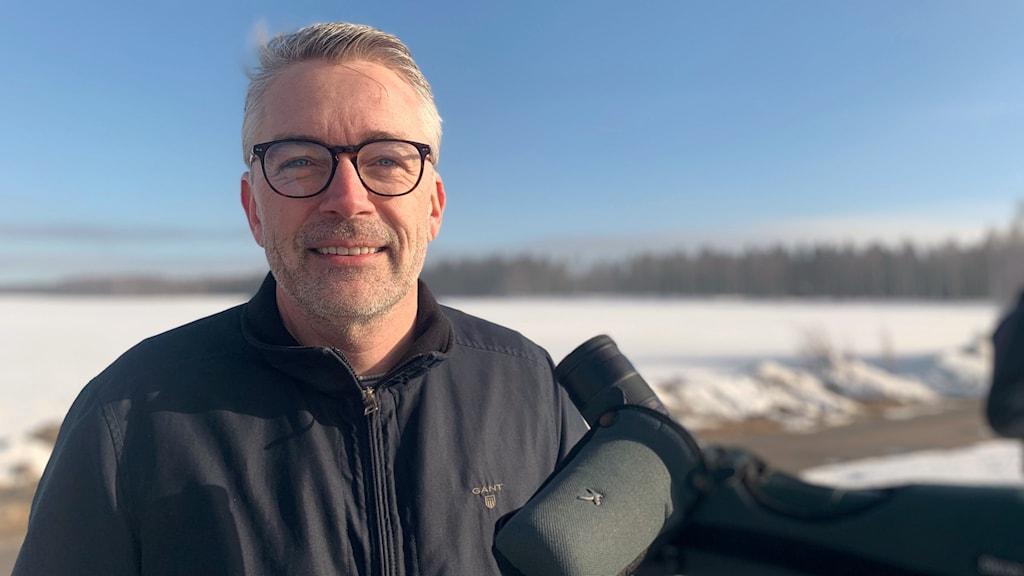 Tomas Brodin med en tubkikare på Degernässlätten. En klar morgon med blå himmel och snö på marken.