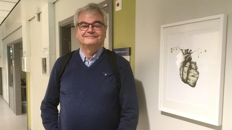 Stefan Söderberg står bredvid en tavla med ett hjärta på. Forskningsprojektet SCAPIS.